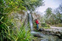Een kerel in een rood jasje fotografeert op een smartphone een waterval royalty-vrije stock foto