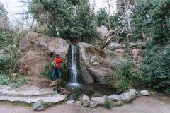 Een kerel in een rood jasje fotografeert op een smartphone een waterval royalty-vrije stock afbeeldingen