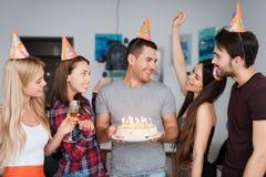 Een kerel` s verjaardag en zijn vrienden wensen hem geluk De gasten bevinden zich rond het feestvarken De kerel houdt a Royalty-vrije Stock Afbeelding