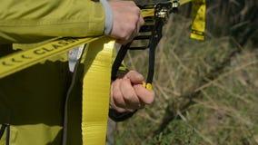 Een kerel trekt een slacklin door een kabel of een slingline te installeren in evenwicht te brengen close-up op het stock footage