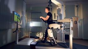 Een kerel volgt TV-avatar tijdens zijn exoskeleton opleiding stock video