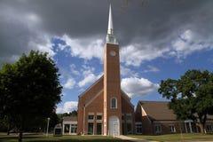 Een kerk onder stormachtige blauwe hemel Stock Afbeeldingen
