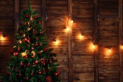 Een Kerstboom met speelgoedornamenten wordt verfraaid parelt rode slinger op houten bruine muur die copyspace stock afbeeldingen