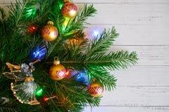 Een Kerstboomtak met speelgoed en lichten naast a wordt verfraaid die stock foto's