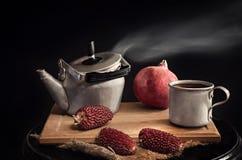 Een ketel en een mok met thee en fruit op een Hakbord Stock Foto's