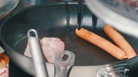 Een keuken in de koffie Het maken van een Engels ontbijt in de pan Bacon en worsten stock video