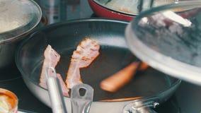 Een keuken in de koffie Het maken van een Engels ontbijt in de pan Openend het deksel, keer het bacon en de worsten om stock video