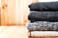 Een keurige stapel van gebreide warme grijze deken of sweaters, wit op een houten achtergrond stock foto