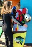 Een kielzog inschepend meisje verzamelt materiaal - een wakeboard, laarzen, een helm en een wakesurfing vest stock foto