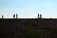 Een kiezelsteenstrand en unrecognisable mensen die op de horizon lopen royalty-vrije stock afbeelding