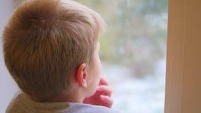 Een kind bekijkt uit het venster de sneeuwval stock videobeelden