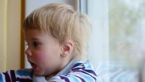 Een kind bekijkt uit het venster de sneeuwval stock footage