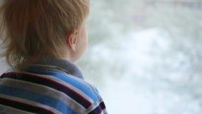 Een kind bekijkt uit het venster de sneeuwval stock video