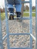 een kind beklimt op een ladder van een dia Royalty-vrije Stock Afbeeldingen