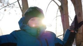 Een kind bevindt zich dichtbij een boom op de achtergrond van zonlicht Het landschap van de winter stock videobeelden