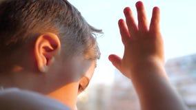Een kind bevindt zich dichtbij een een venster en het letten op sneeuw die op de straat vallen De close-uphand op het glasvenster stock footage