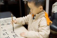 Een kind dat Chinese Kalligrafie schrijft stock foto