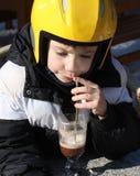 Een kind dat een hete chocolade van de helmdrank draagt Royalty-vrije Stock Afbeeldingen