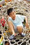 Een kind dat een wildernisgymnastiek beklimt. Stock Foto's