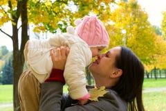 Een kind in de herfst op de aard en de moeder stock afbeeldingen