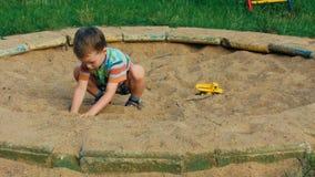 Een kind die in de zandbak spelen stock videobeelden