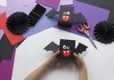 Een kind die Halloween-decoratie van gekleurd document maken stock foto's