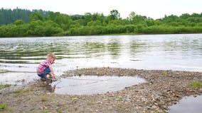 Een kind die op de banken van de rivier, het Mooie de zomerlandschap spelen Openlucht recreatie stock video