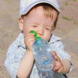 Een kind drinkt water van een fles Het kind, de jongen, dooft stock foto