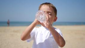 Een kind drinkt water van een transparante plastic fles op een zonnig zandig strand op een zonnige dag stock footage