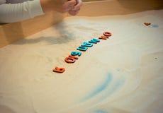 Een kind in een zandbak maakt de brieven van de Russische alfabet onderwijsactiviteiten voor op jonge geitjes Stock Fotografie