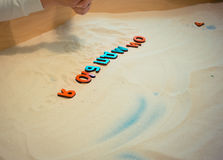 Een kind in een zandbak maakt de brieven van de Russische alfabet onderwijsactiviteiten voor op jonge geitjes Stock Afbeeldingen