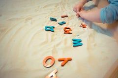 Een kind in een zandbak maakt de brieven van de Russische alfabet onderwijsactiviteiten voor op jonge geitjes Stock Afbeelding