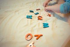 Een kind in een zandbak maakt de brieven van de Russische alfabet onderwijsactiviteiten voor op jonge geitjes Royalty-vrije Stock Fotografie