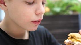 Een kind eet een broodje met een kotelet en kaas in een snel voedselrestaurant stock video