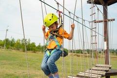 Een kind in het eenvormige hangen op een kabel op een kabelwagen in een extreem park royalty-vrije stock afbeeldingen