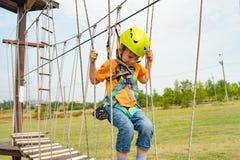 Een kind in het eenvormige hangen op een kabel op een kabelwagen in een extreem park stock afbeeldingen