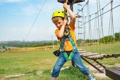 Een kind in het eenvormige hangen op een kabel op een kabelwagen in een extreem park royalty-vrije stock afbeelding