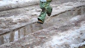 Een kind in het Park die op vulklei lopen Plonsen van waterverspreiding op de partijen Vermaak, openluchtsporten stock video