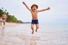 Een kind in een hoed springt op de oceaan - Aziatische jongen in een hoed, vage achtergrond royalty-vrije stock foto's
