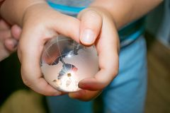 Een kind houdt de Bal van de Glasaarde Royalty-vrije Stock Afbeeldingen
