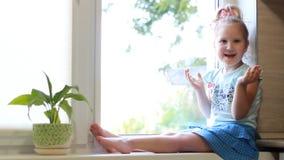 Een kind kijkt uit het venster, glimlachen, die geen gebaar tonen Het concept verwachting stock footage