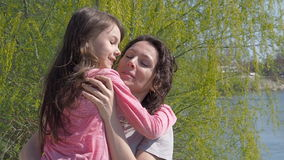 Een kind koestert haar moeder op de rivierbank Gelukkige familie in aard Mamma en dochter in de verse lucht Een zonnige dag stock footage