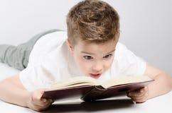 Een kind leest boek het liggen stock afbeeldingen
