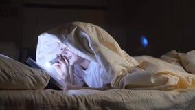 Een kind leest een boek onder dekens met een flitslicht bij nacht Enthousiaste jongen stock footage
