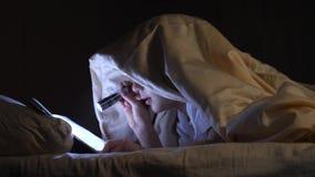Een kind leest een boek onder dekens met een flitslicht bij nacht Enthousiaste jongen stock videobeelden