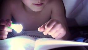 Een kind leest een boek onder dekens met een flitslicht bij nacht jongen met licht haar en blauwe ogen stock videobeelden