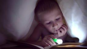Een kind leest een boek onder dekens met een flitslicht bij nacht jongen met licht haar en blauwe ogen stock footage