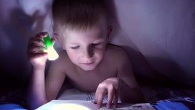 Een kind leest een boek onder dekens met een flitslicht bij nacht jongen met licht haar en blauwe ogen stock video