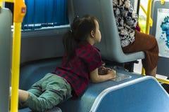 Een kind legt op de zetel in de het schudden bus Alleen royalty-vrije stock afbeelding