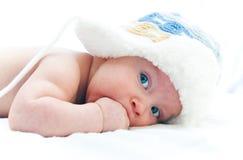 Een kind met blauwe ogen met een hoed Stock Foto